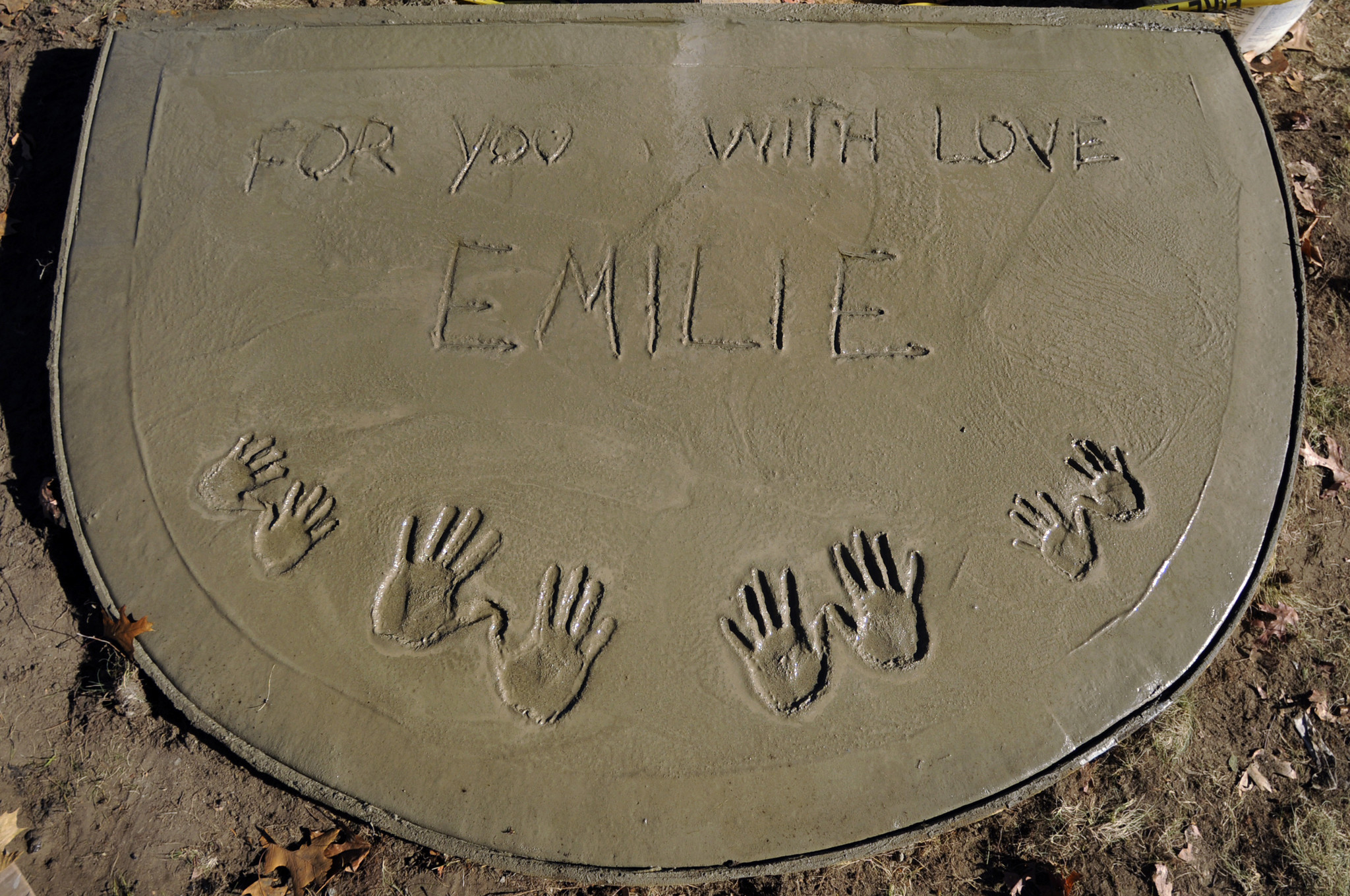 Freshly poured cement imprinted with the handprints of the Parker family and a tribute to Emilie Parker marks the entrance to Emilie