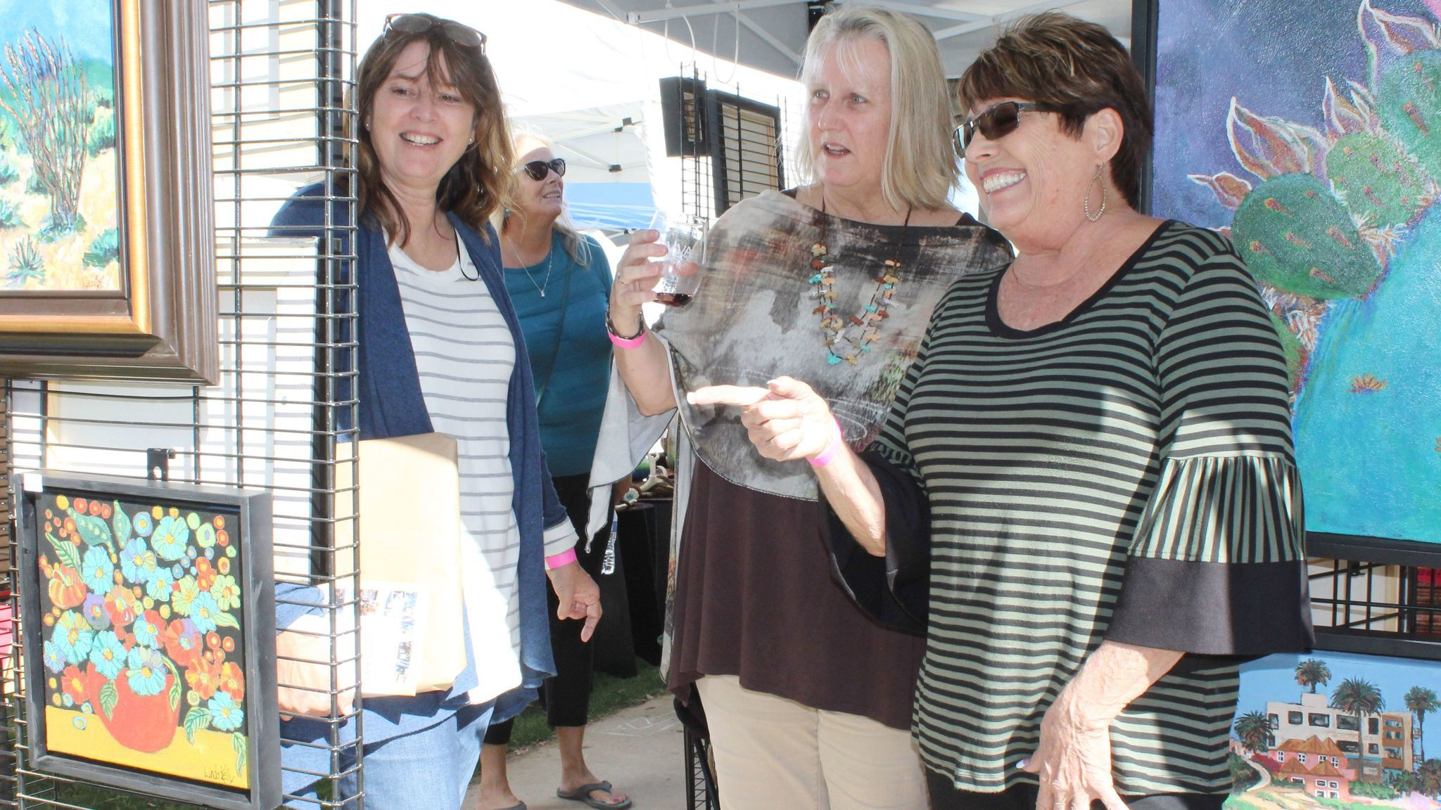 From left, Ramona residents Lori Hardesty and Shelley Gilbert, both 1978 Ramona High School graduates, talk with artist Linda Kelly about one of her works.