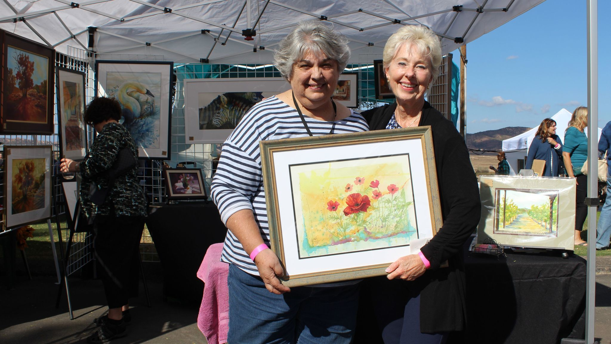 """Solana Beach resident Victoria Smith, right, purchases Ramona artist Lynette Bredow's watercolor titled """"Field of Poppies."""""""