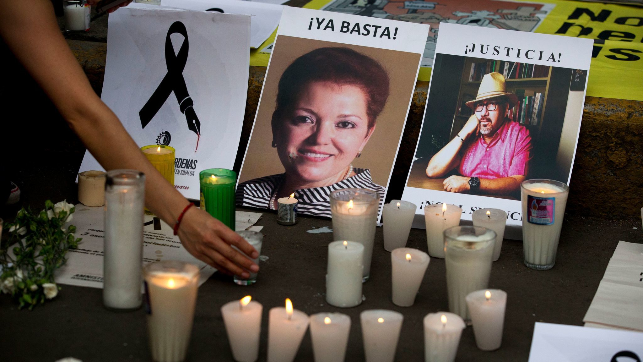 FILE - In this May 16, 2017 file photo, a woman places a candle in front of pictures of murdered jou