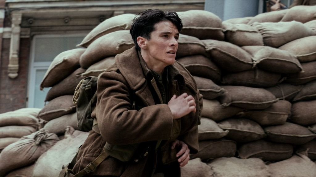 "Fionn Whitehead runs toward the beach in the opening moments of ""Dunkirk."""