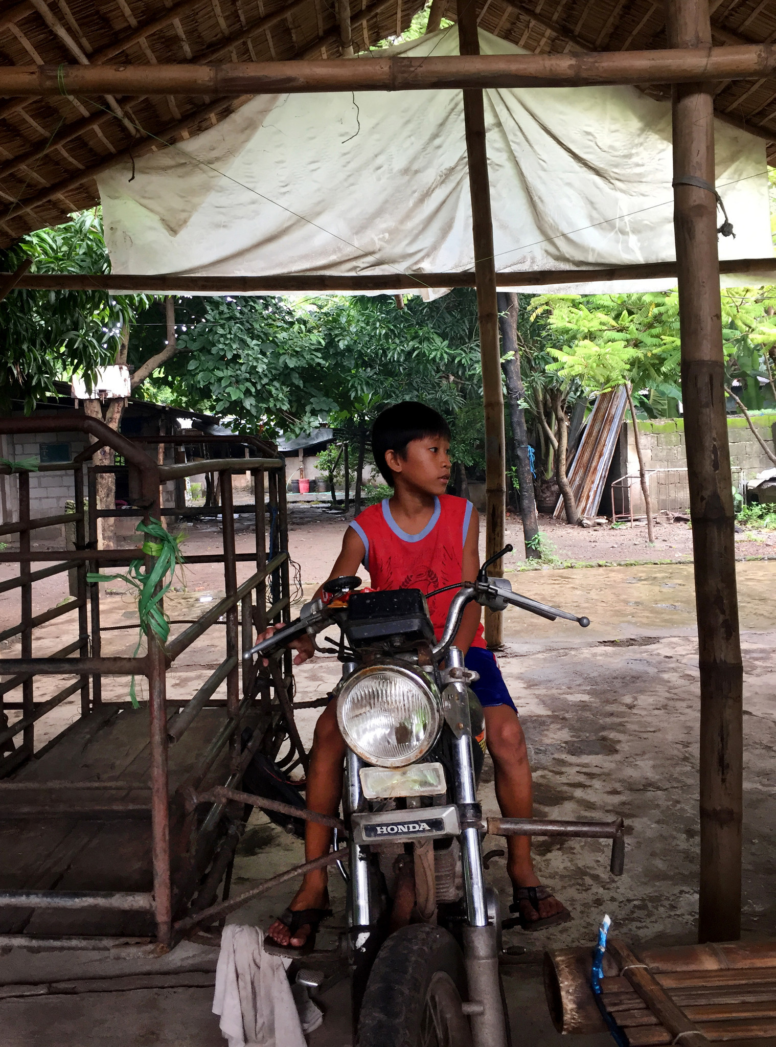 Deceased environmental activist Gloria Capitan's grandson Jerson, 8, plays on a motorbike at the fam