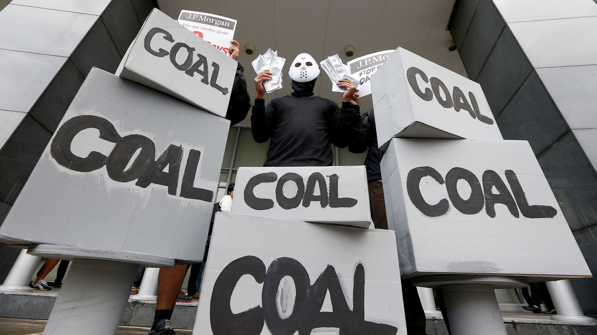 A masked environmental activist wags mock dollars bills during a protest outside the JP Morgan Chase