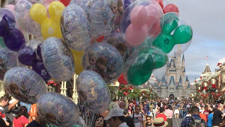 A Disney World employee sells balloons at the crowded Magic Kingdom park after Christmas.