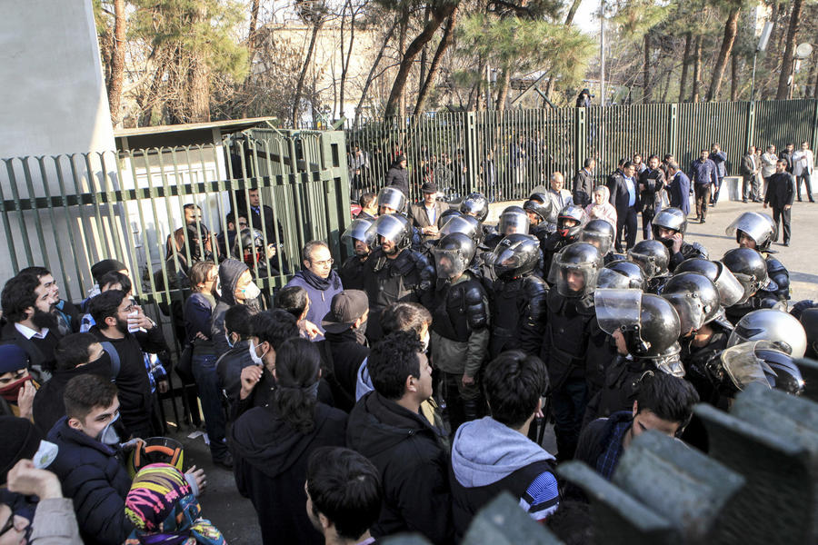 Anti-riot police prevent university students from joining other protesters in Tehran on Dec. 30. (Associated Press)