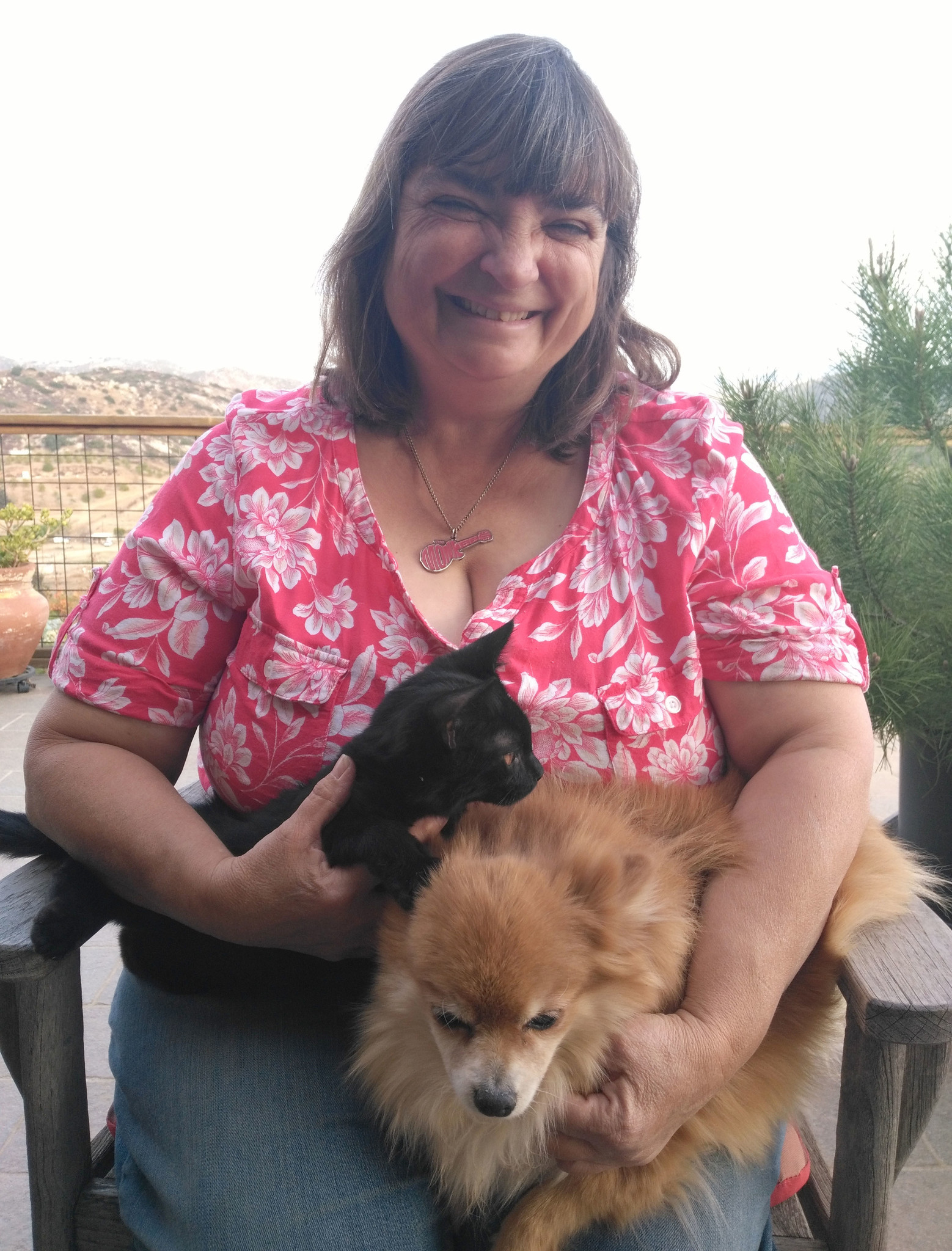 Ramona resident Regina Elling relaxes with a dog and a kitten she cares for temporarily while she strives to find them a permanent home.