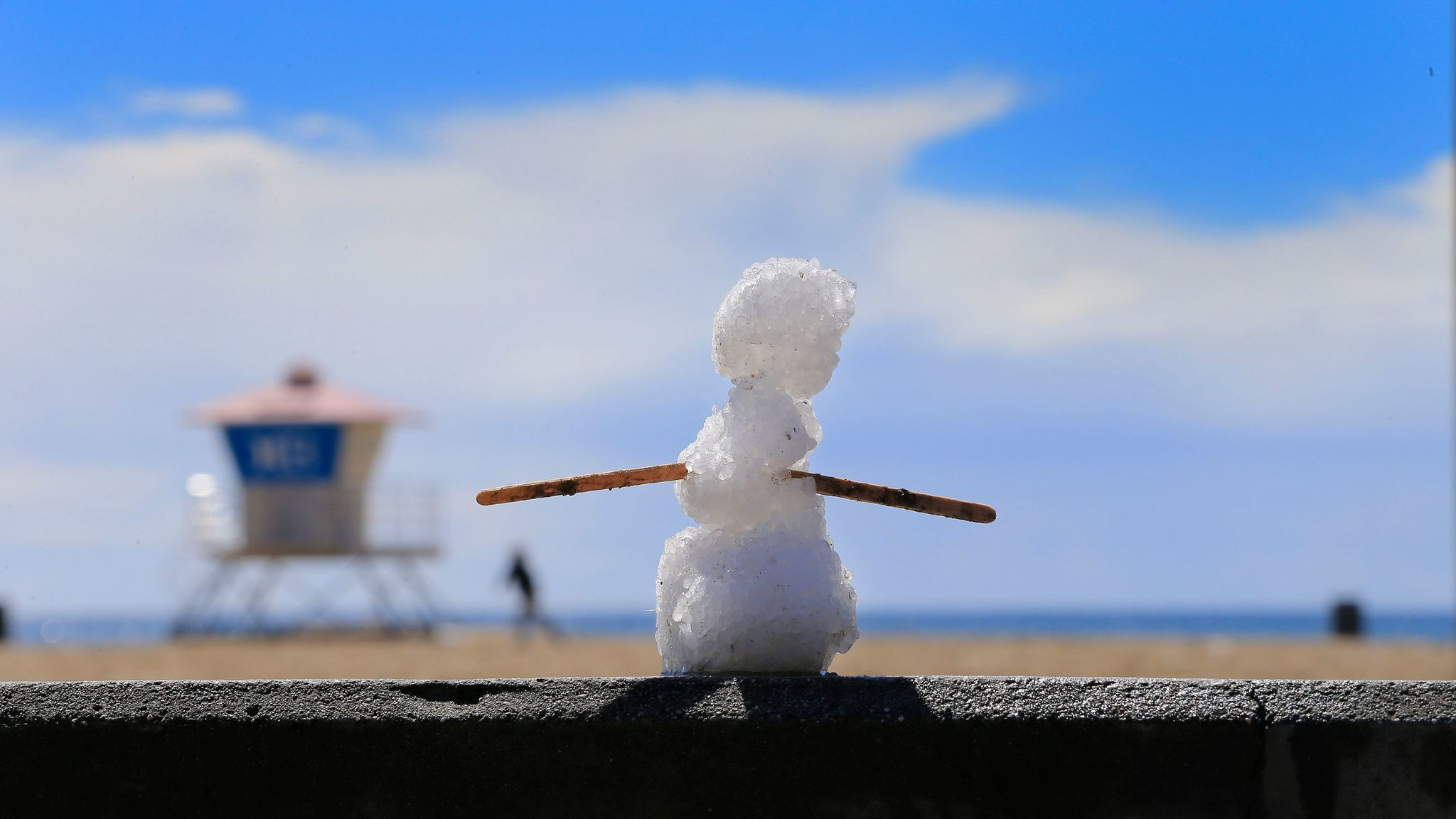 HUNTINGTON BEACH, CA MARCH 2, 2015: A snowman made of hail stands amid a rare sight of a blanket o