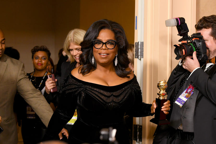 Oprah Winfrey arrives with the Cecil B. DeMille Award in the press room at the Golden Globes on Sunday. (Kevin Winter / Getty Images)