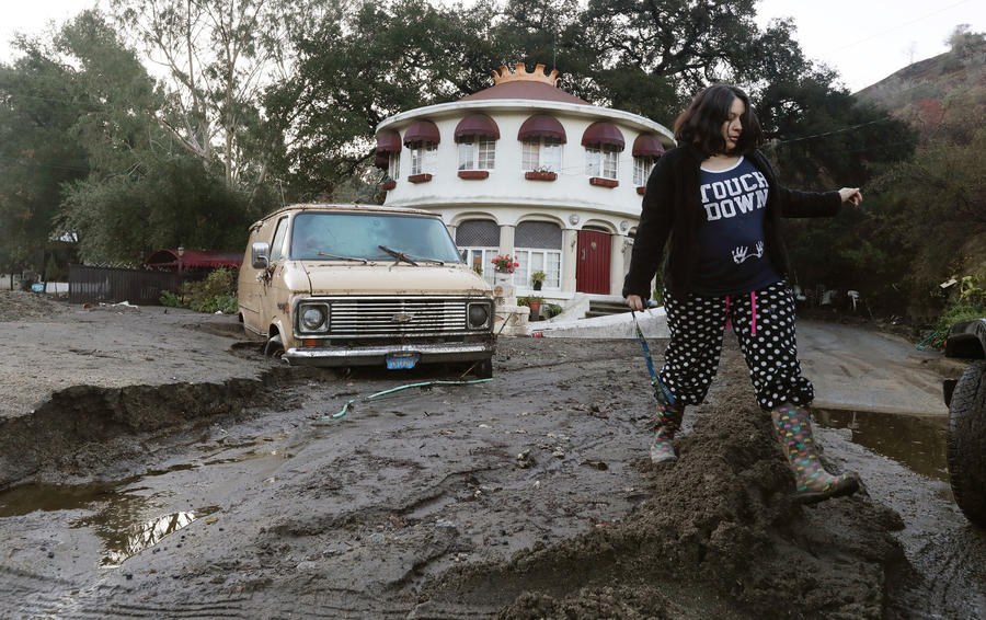 A woman trudges through mud piled on La Tuna Canyon Road after checking on her neighbor whose house was blocked by a mudslide that struck the area. (Irfan Khan / Los Angeles Times)