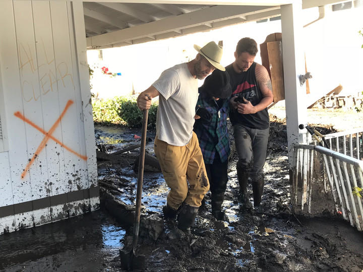 Neighbors help an 88-year-old woman, Gloria Hebert, evacuate her Montecito home. None