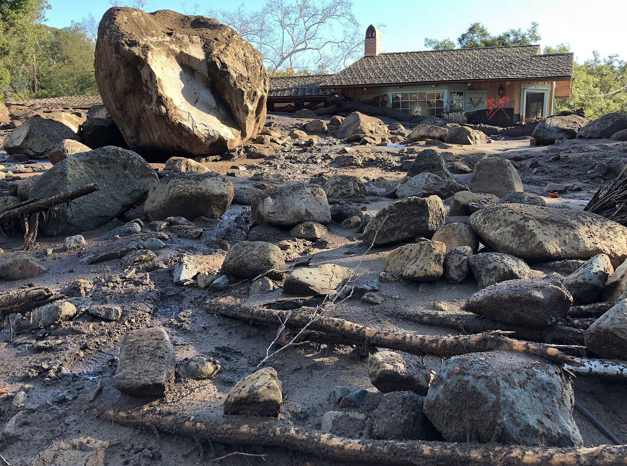 Boulders, logs and a carpet of mud in front of a house along San Ysidro Creek near East Valley Road in Montecito. (Mike Eliason / Santa Barbara County Fire Department)