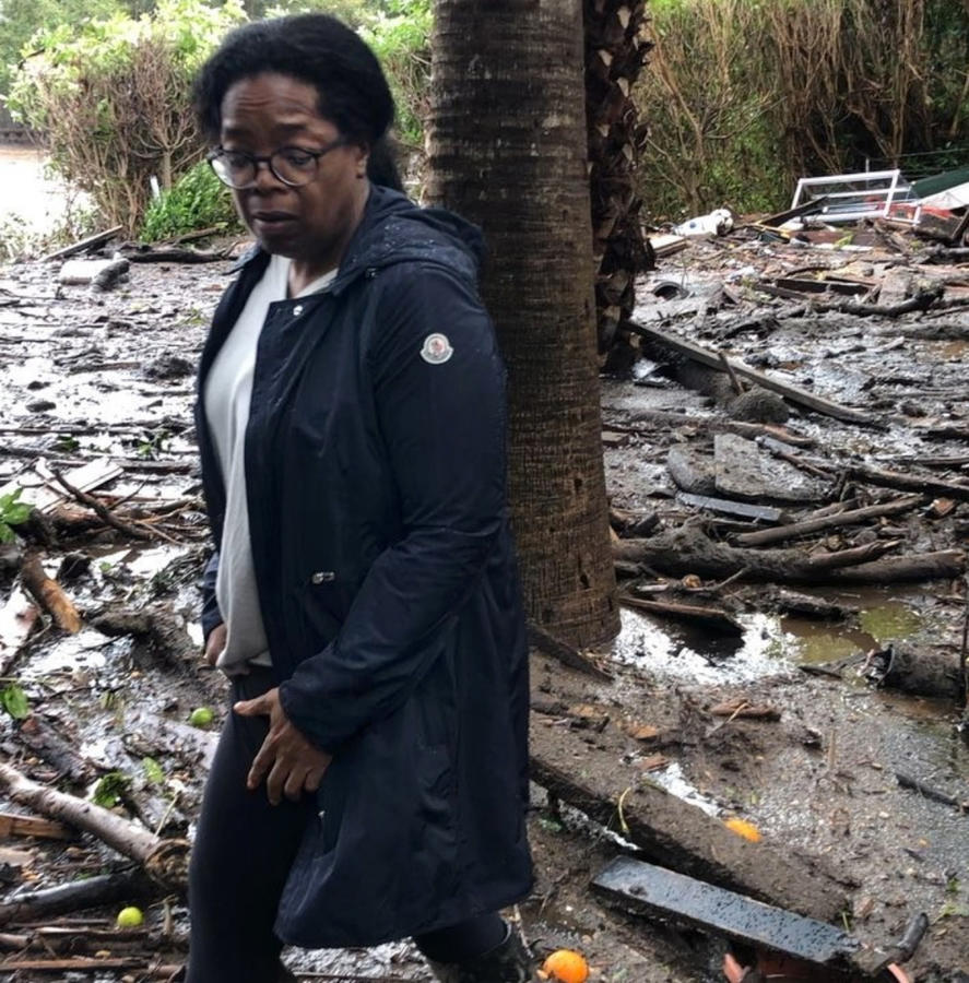 Oprah Winfrey stands amid debris on Wednesday as she surveys her neighbors' property in Montecito. (Oprah Winfrey via Associated Press)