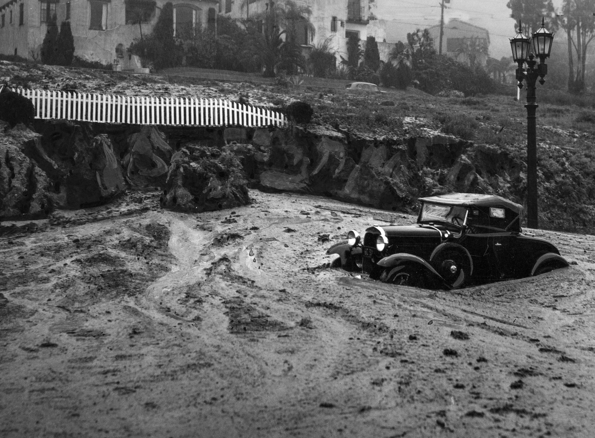 March 2, 1938: Mud slide at Harper Avenue and Sunset Boulevard caught this automobile and closed the