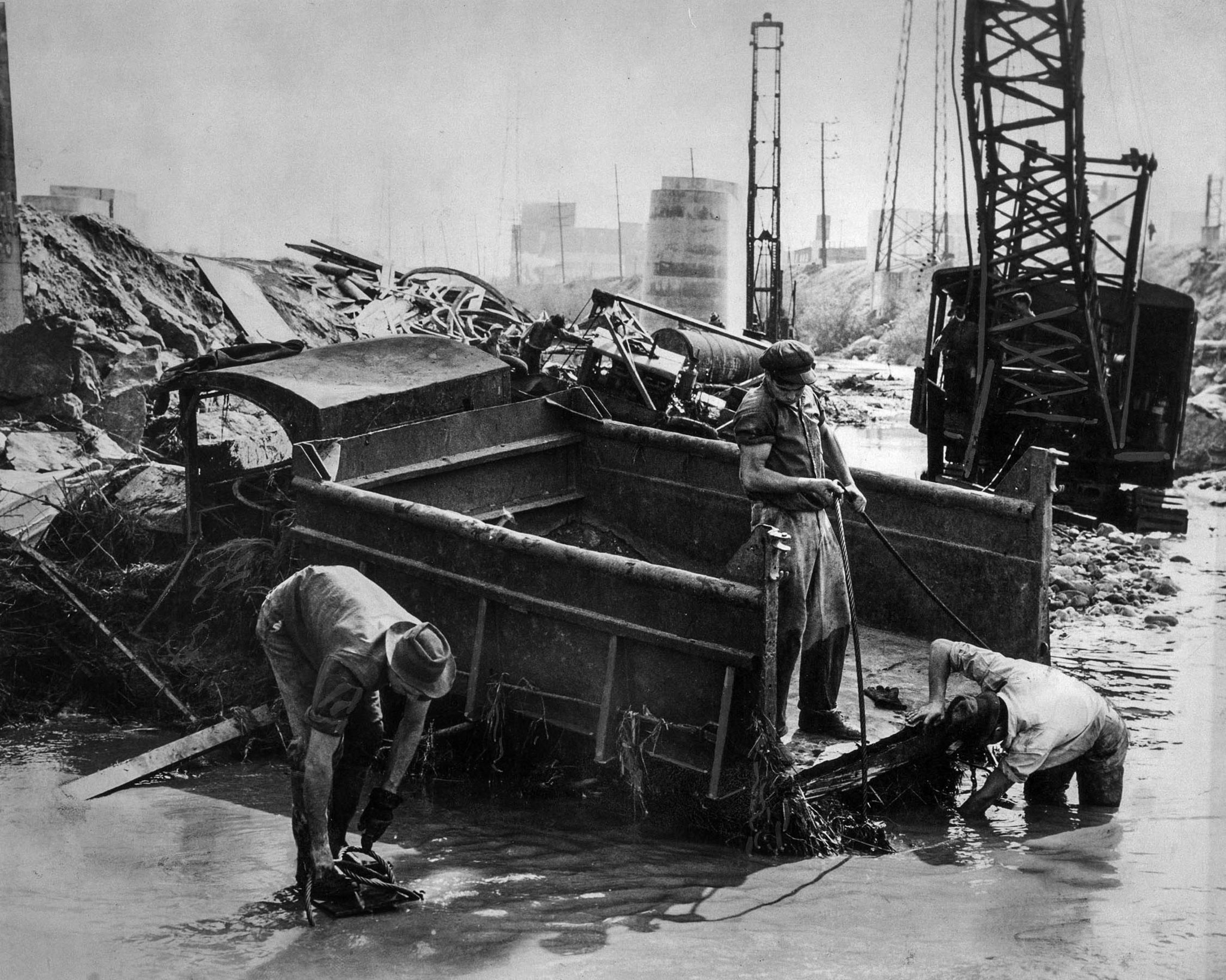 March 2, 1938: Salvage crew trys to dig out gravel truck damaged by flooding along the Los Angeles R
