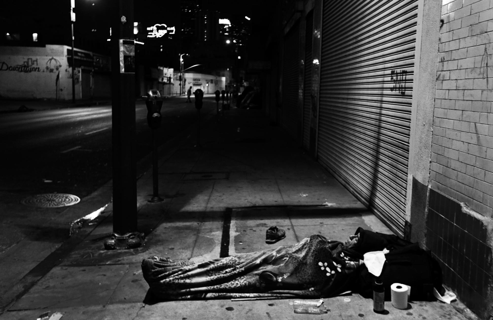 A man sleeps on the sidewalk in downtown Los Angeles.