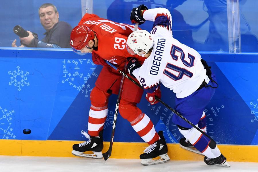 Russia's Ilya Kablukov, left, checks Norway's Henrik Odegaard in a men's quarterfinal hockey game. (Kirill Kudryavtsev / AFP / Getty Images)