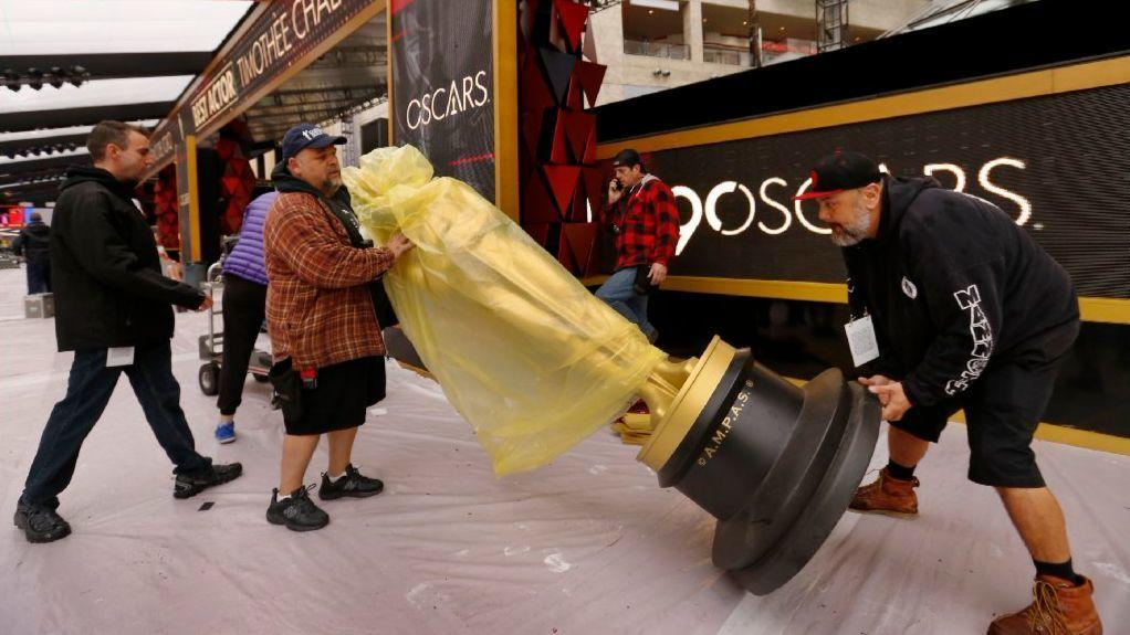 Christian Rosso, left, and Makai Greer carry an Oscar statue to the red carpet on Friday in advance of Sunday's awards.. (Al Seib / Los Angeles Times)