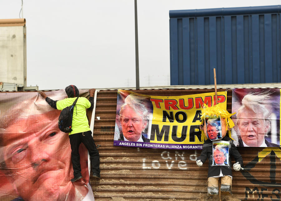 A Trump protester hangs a banner on the Mexico side of the border. (Wally Skalij / Los Angeles Times)