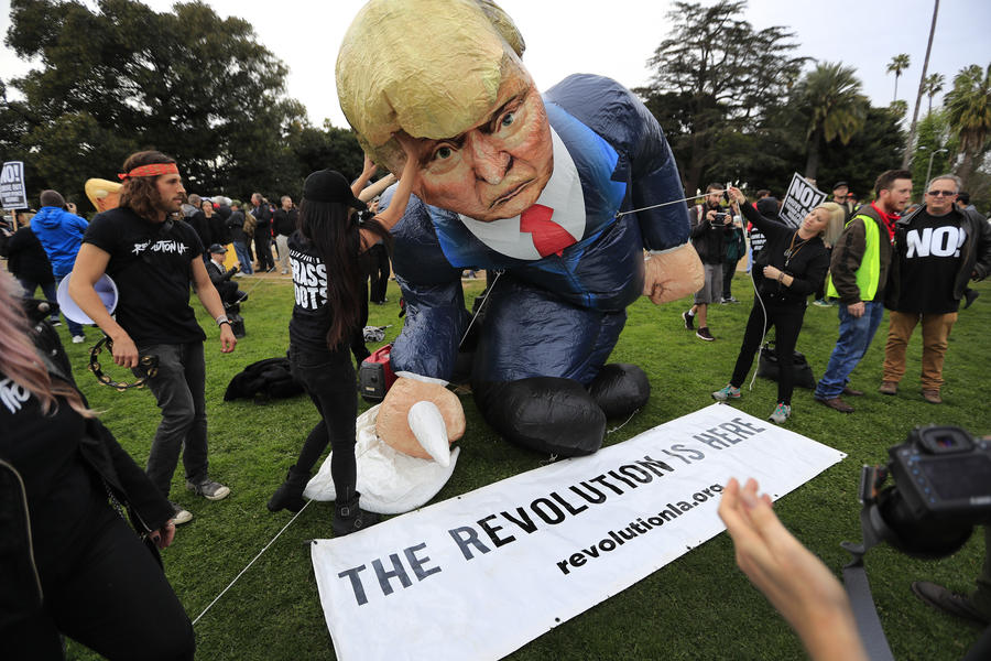 Tourists sightseeing in Beverly Hills had another spectacle to see Tuesday as an anti-Trump rally took place in Beverly Gardens Park. (Allen J. Schaben)