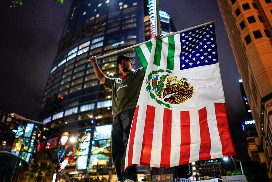 Jesse Madera holds a flag that is an amalgamation of the U.S. and Mexico flags while he and other people chant, protesting President Trump. (Kent Nishimura/Los Angeles Times)