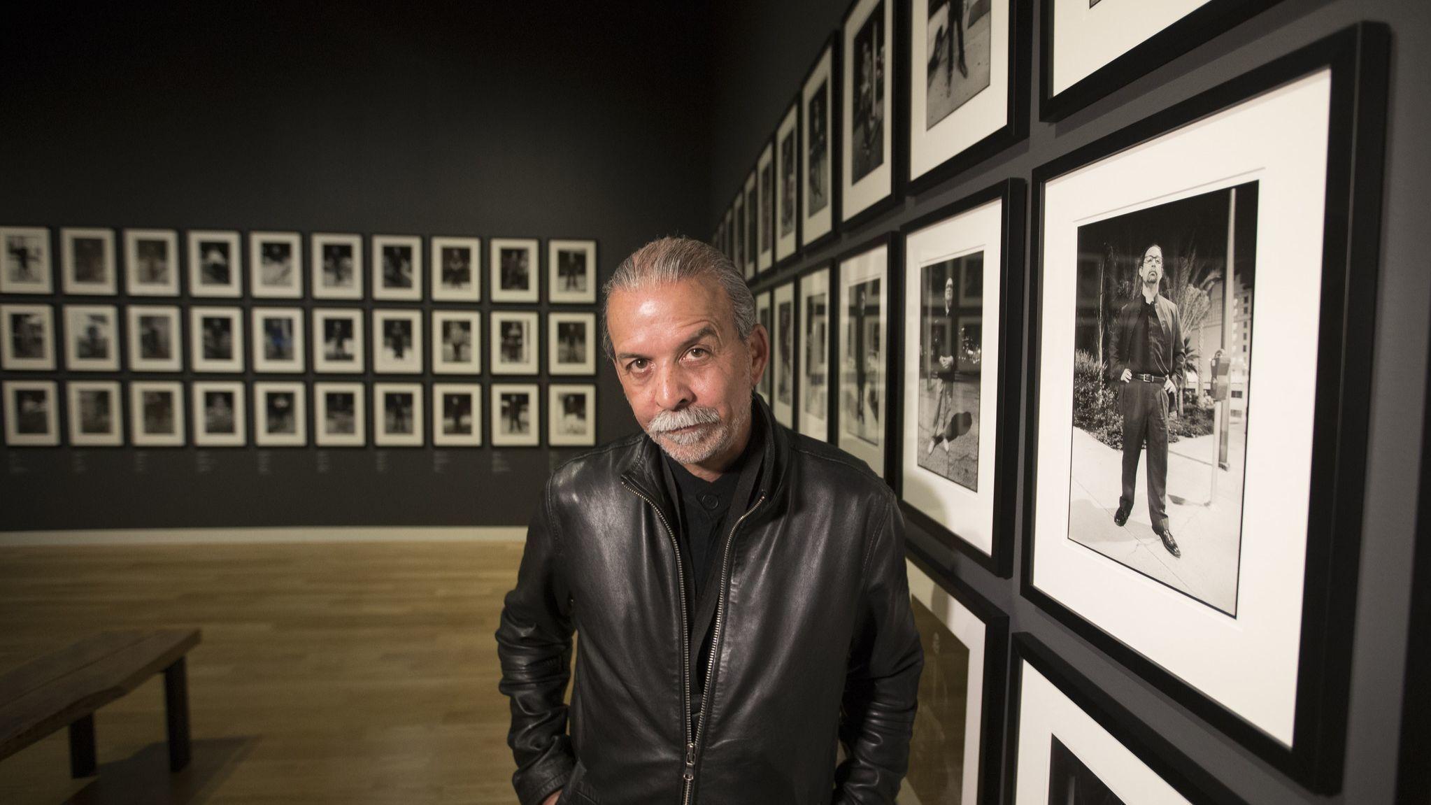 Photographer Harry Gamboa Jr. stands amid his portraits