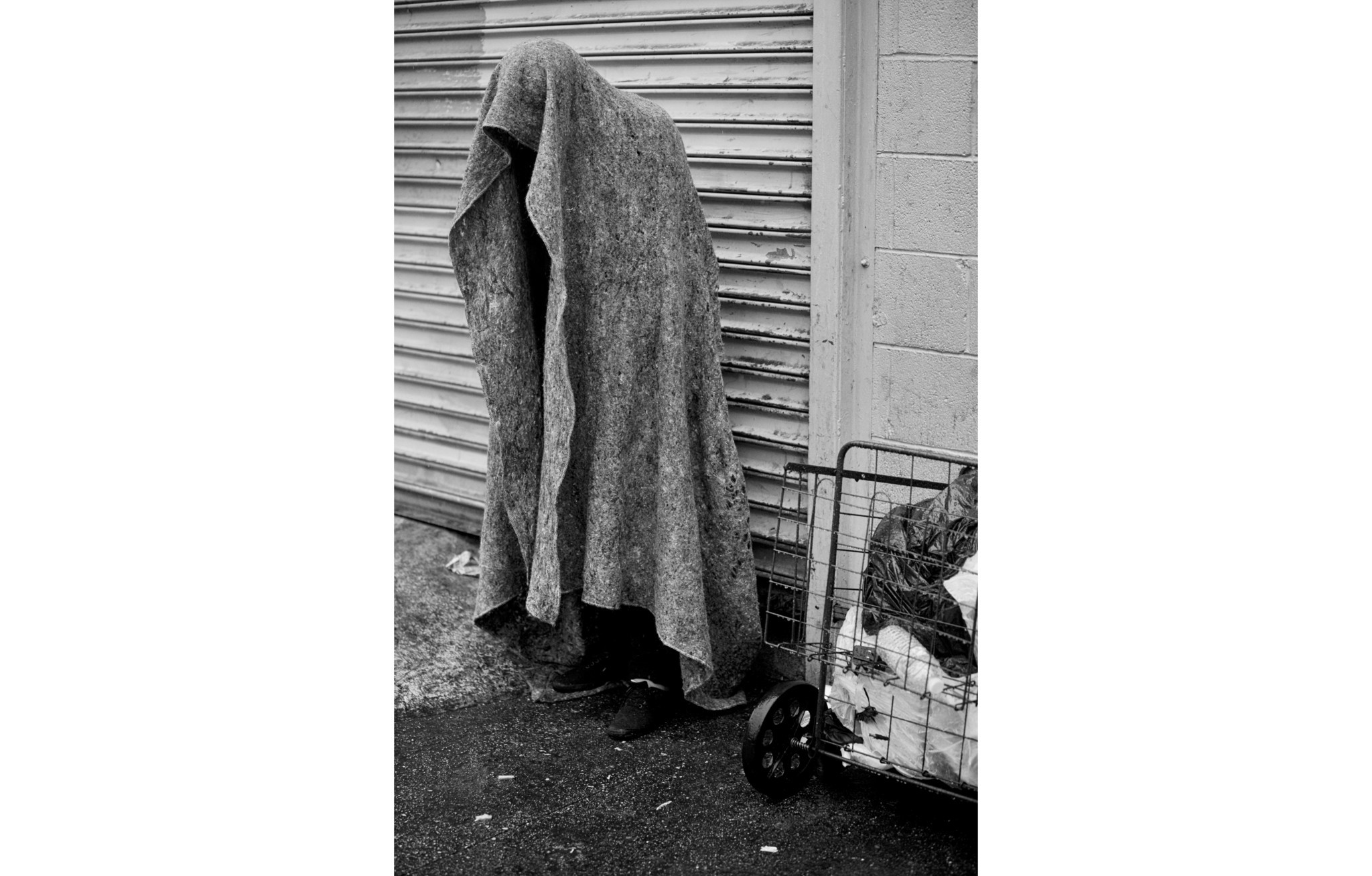 LOS ANGELES, CA - DECEMBER 2, 2014: A person stands beneath a blanket in the rain trying to keep dry