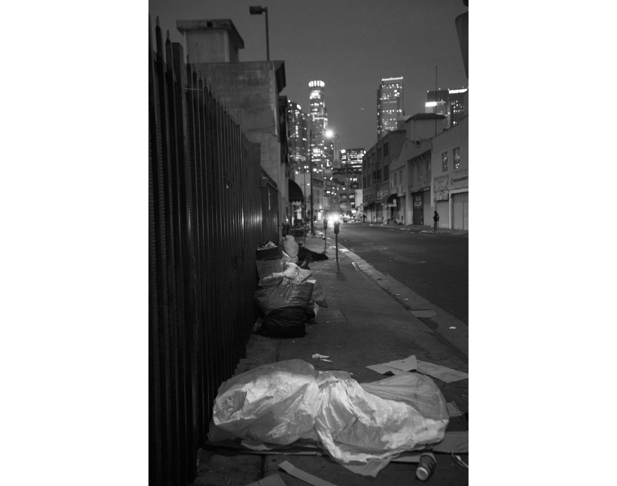 LOS ANGELES, CA NOVEMBER 15, 2017: At dawn people are sleeping on the sidewalk wrapped in tarps and