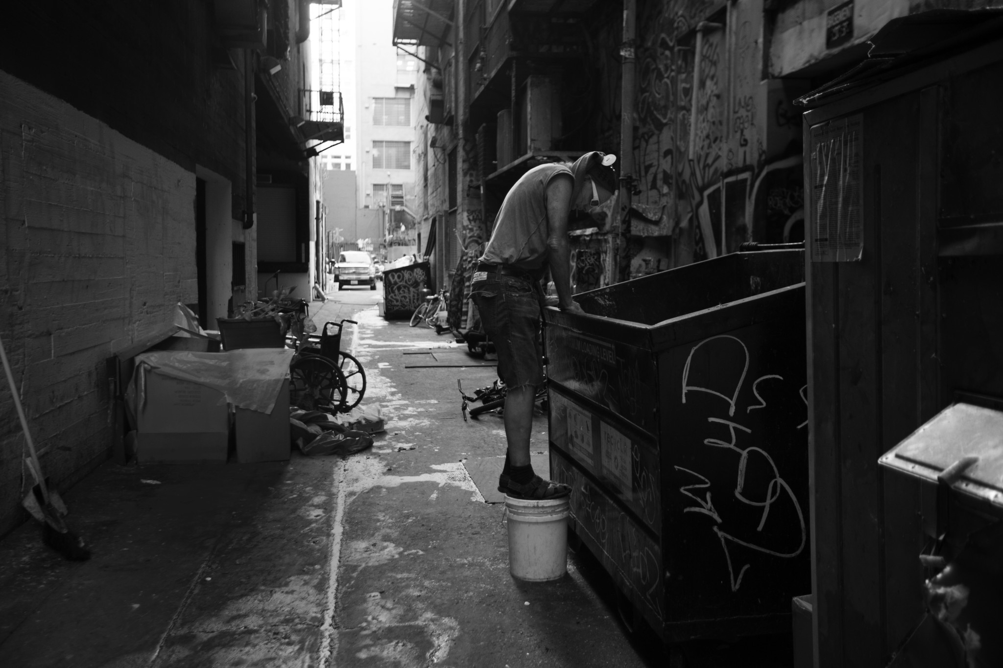LOS ANGELES , CA NOVEMBER 17, 2017: A man climbs into the garbage bin in an alley in Los Angeles, CA