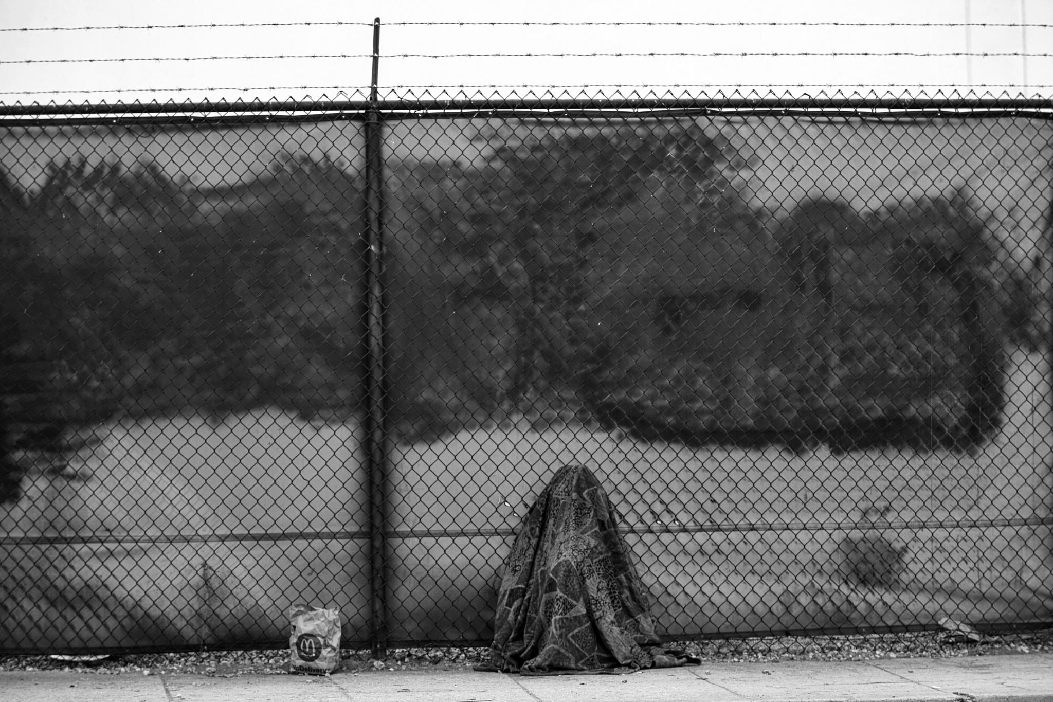 LOS ANGELES, CA NOVEMBER 8, 2017: A homeless person sits under a blanket next to a McDonald's bag ne