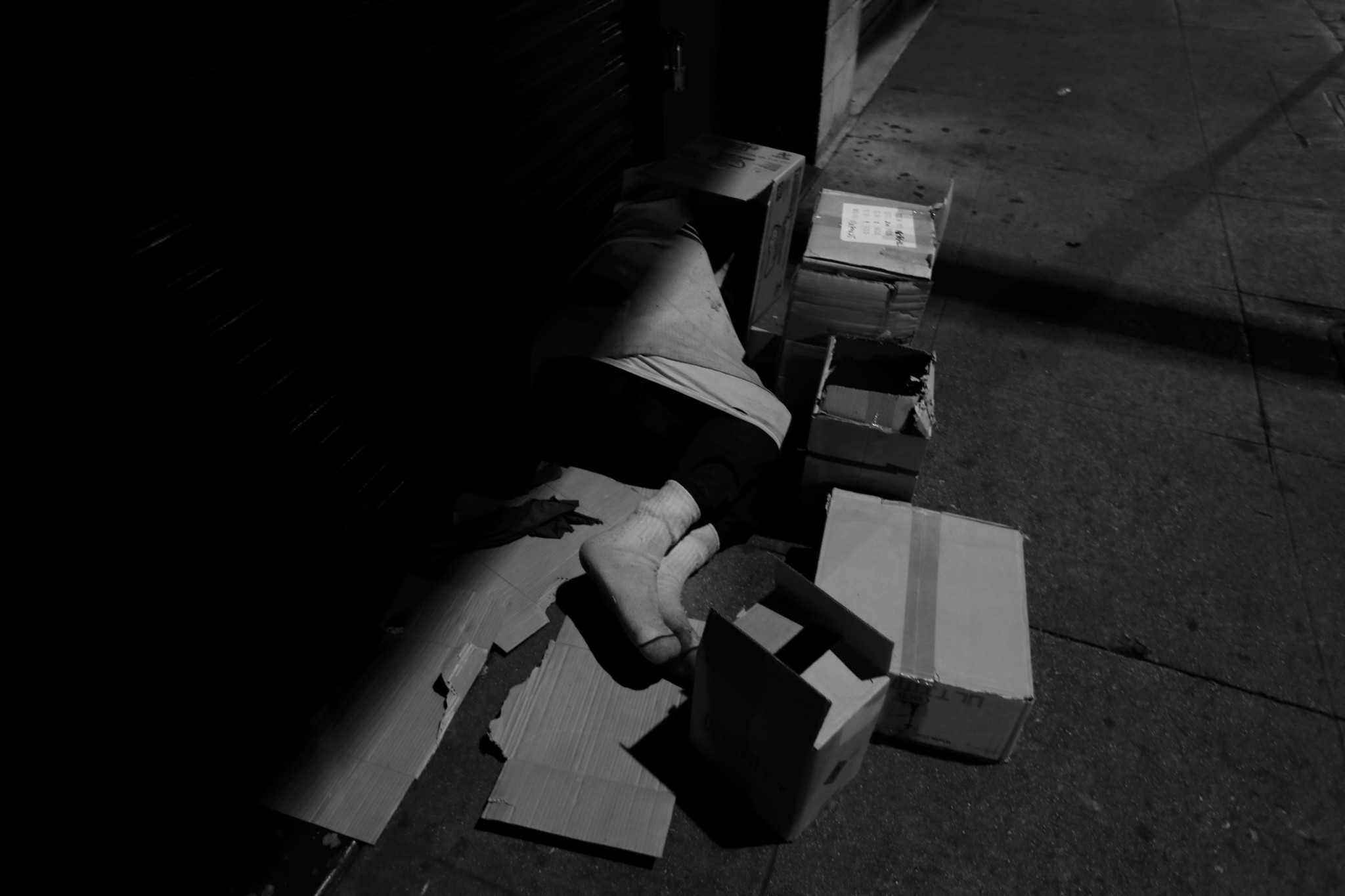 LOS ANGELES, CA February 2, 2018: A person sleeps on a piece of card board, surrounded by boxes o
