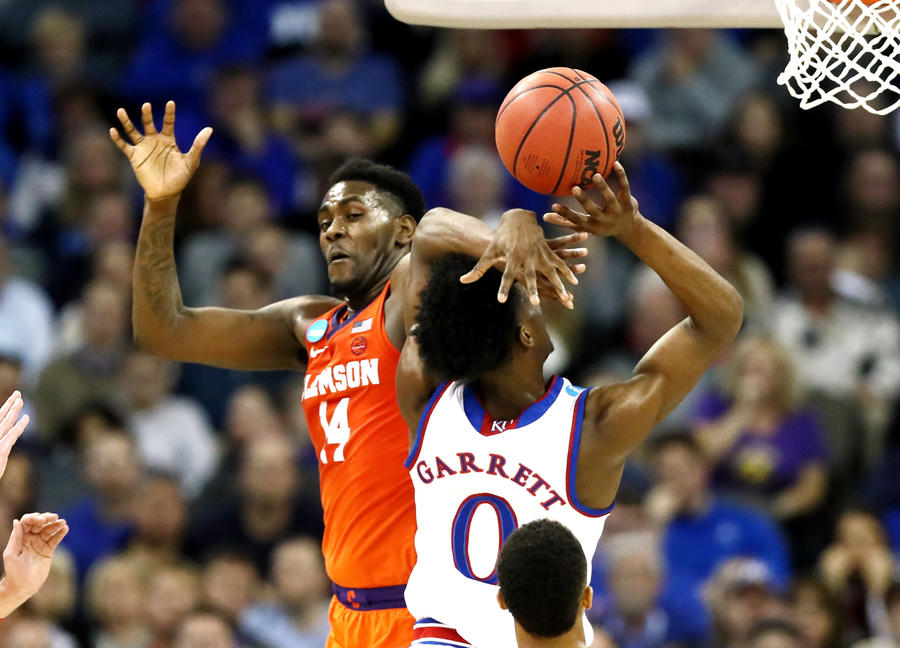 Kansas' Marcus Garrett is fouled by Clemson's Elijah Thomas during the second half Friday. (Jamie Squire / Getty Images)