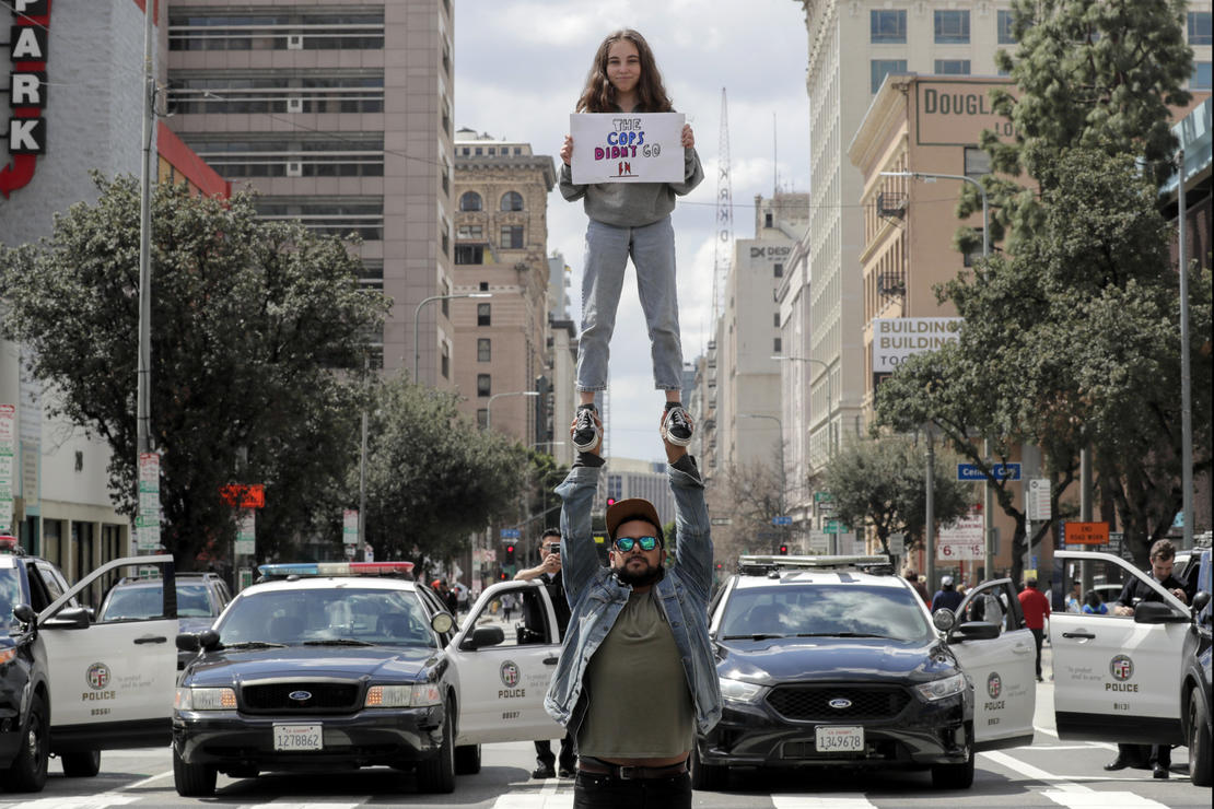 In Los Angeles, Emie Malanaphy, 13, lifted by Jonathan Rea, 29, holds a sign alluding the Florida sheriff's deputy who didn't go in to confront the gunman during the Parkland, Florida shooting. — Photograph: Irfan Khan/Los Angeles Times.
