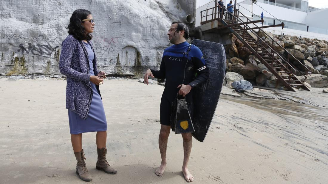 A former lifeguard, Anna Lucía López Avedoy speaks with surfer Gustavo Cortez on the beach at Playas de Tijuana, where runoff from the street above flows to the ocean.
