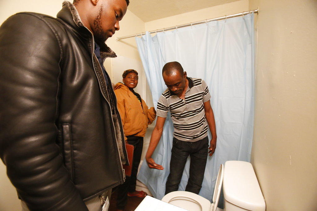 Refugee Ausa Emedi, right, examines a toilet in his family's new apartment in Columbus, Ohio.