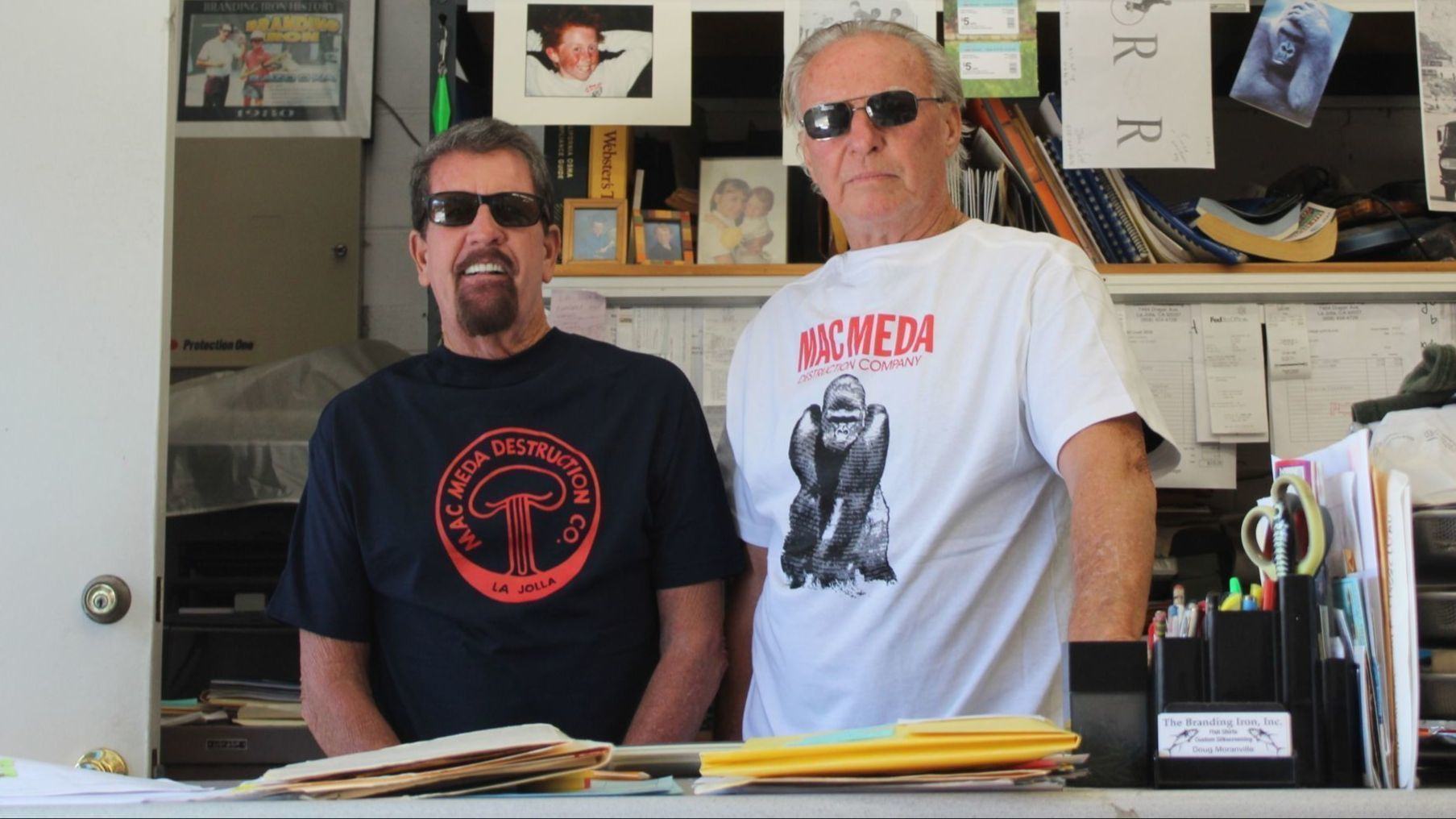 Doug Moranville, left, and Bill Decker reminisce about Mac Meda at Moranville's Branding Iron silkscreening shop..