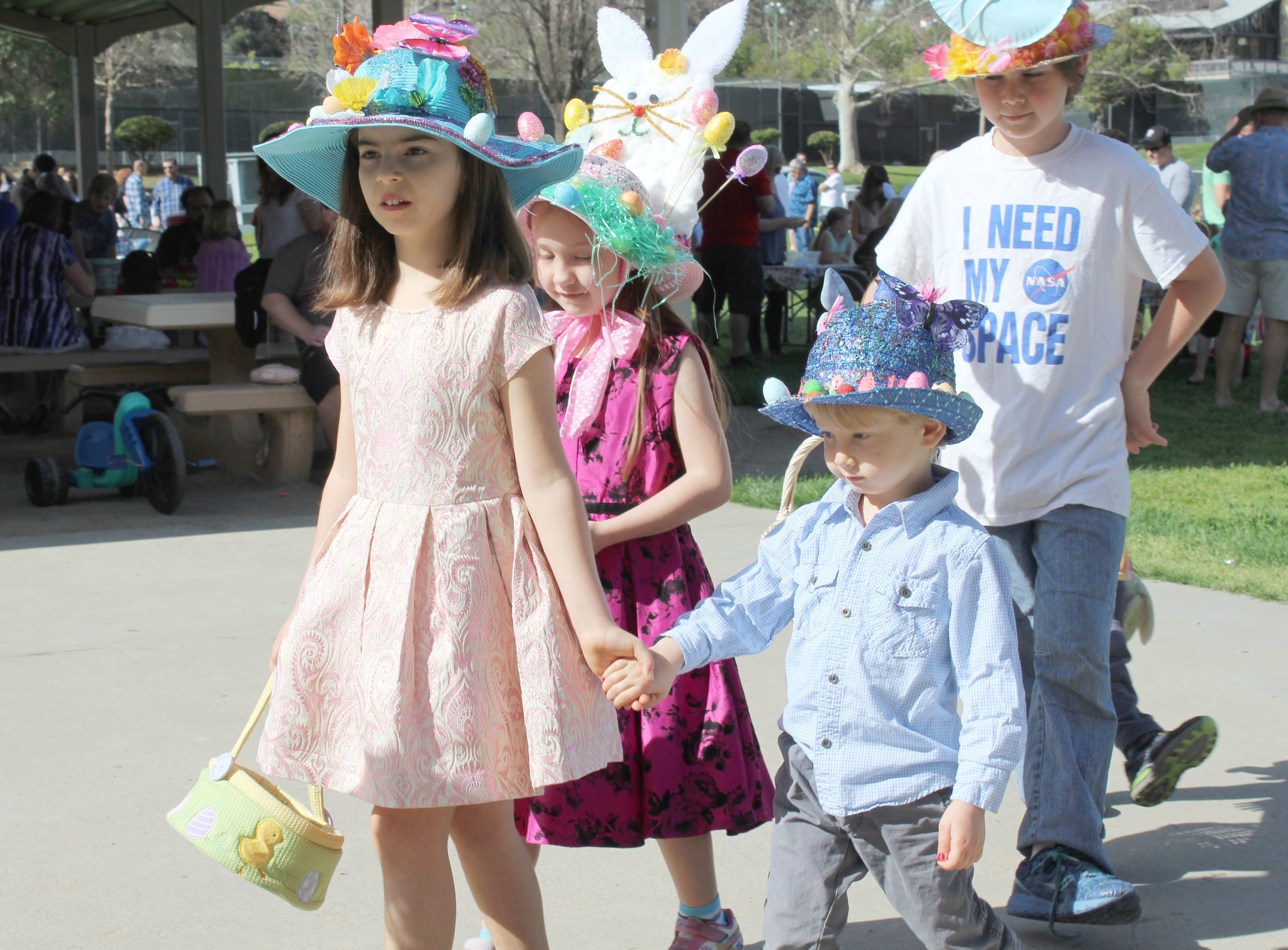 Andre Reese holds his sister Anika's hand as they participate in the Easter Bonnet Parade. Also pictured are Raelynne Larsson and Audie O'Neal.