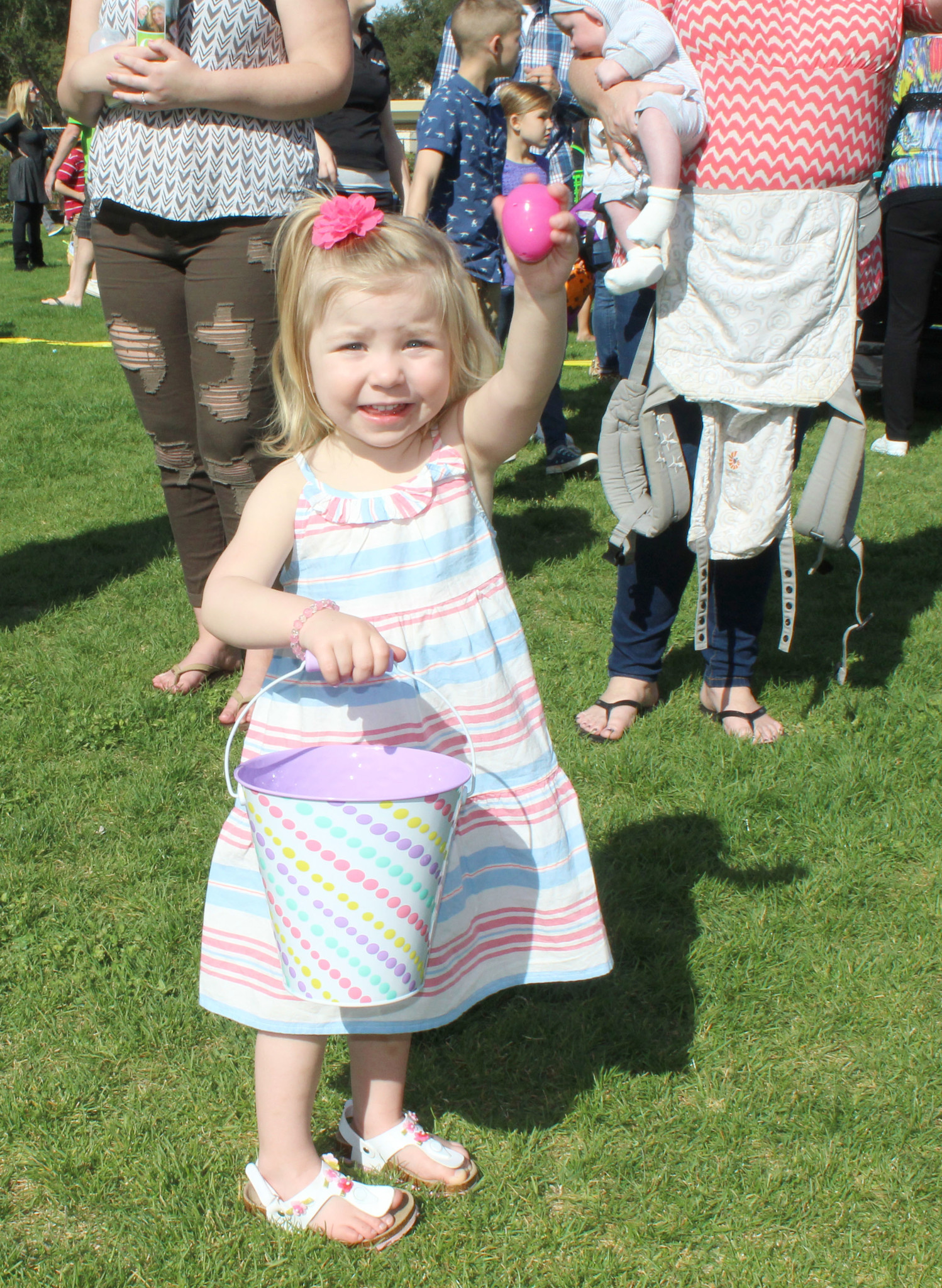 An excited Brooklynn Percival, 2, shows one of the eggs she gathered during the hunt.