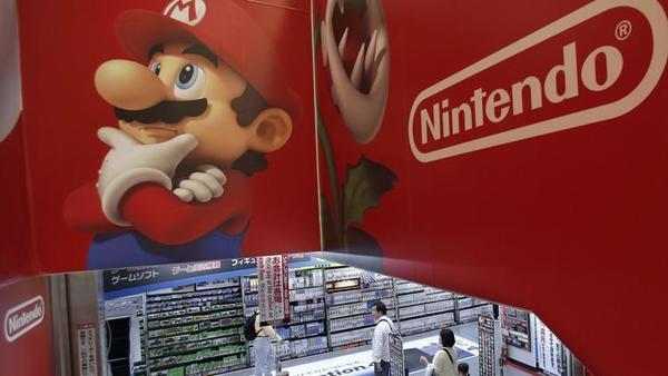 En esta foto de archivo del 7 de mayo de 2014, los compradores caminan bajo el logotipo de los personajes de Nintendo y Super Mario en una tienda de electrónica en Tokio. (Shizuo