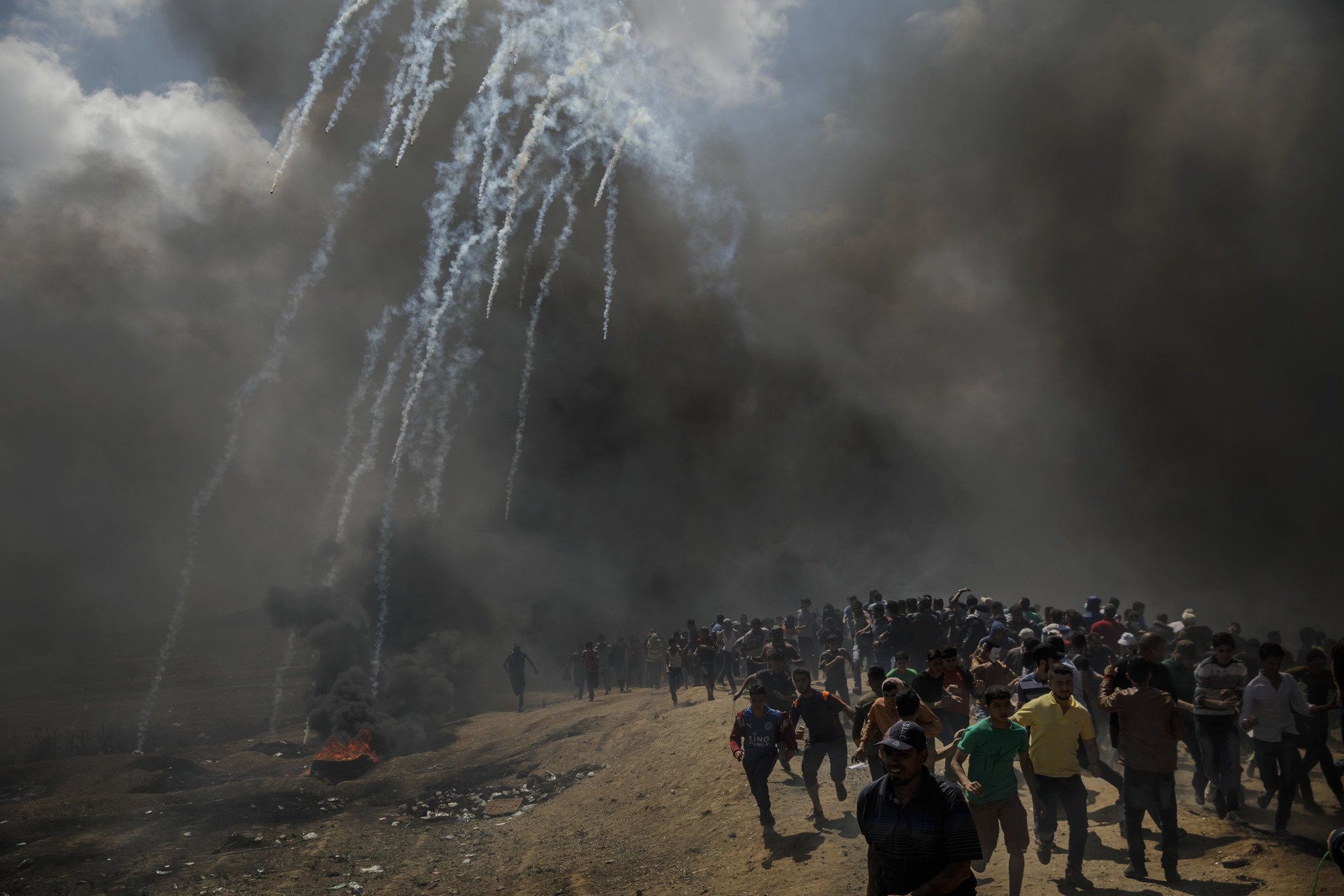 GAZA CITY, GAZA — MONDAY, MAY 14, 2018: Protesters run away from tear gas dispersed by Israeli forc
