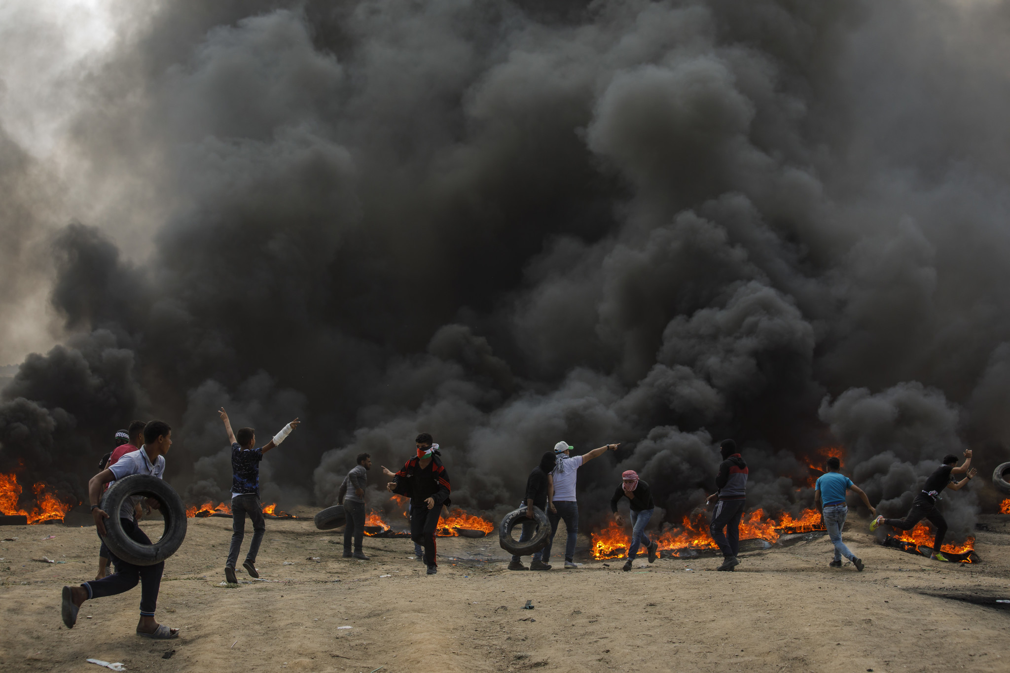 GAZA CITY, GAZA — MONDAY, MAY 14, 2018: Palestinians burn tires to create a smoke column meant to r