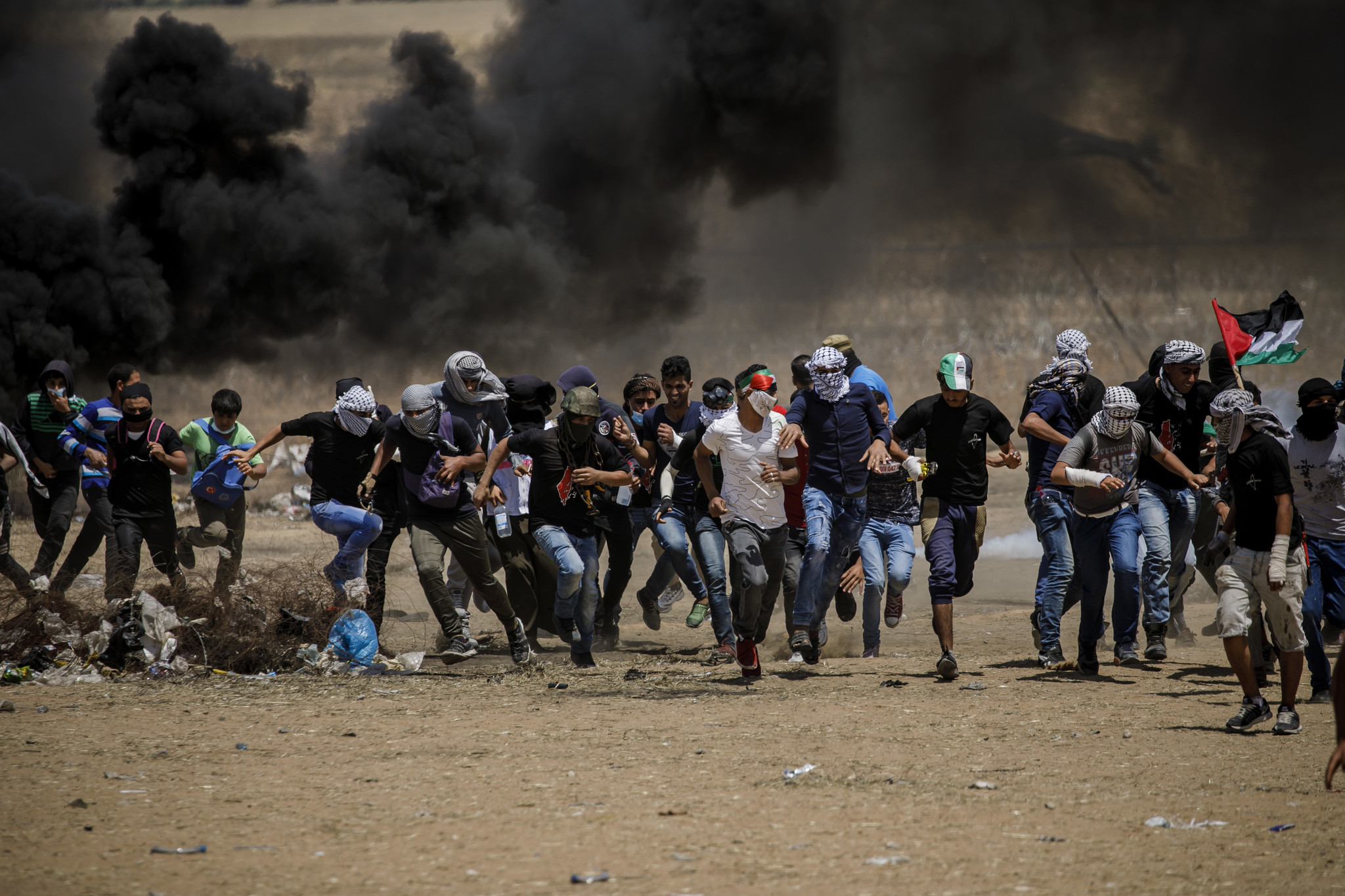 KHAN YOUNIS, GAZA STRIP — FRIDAY, MAY 11, 2018: Palestinian protesters run away from tear gas duri