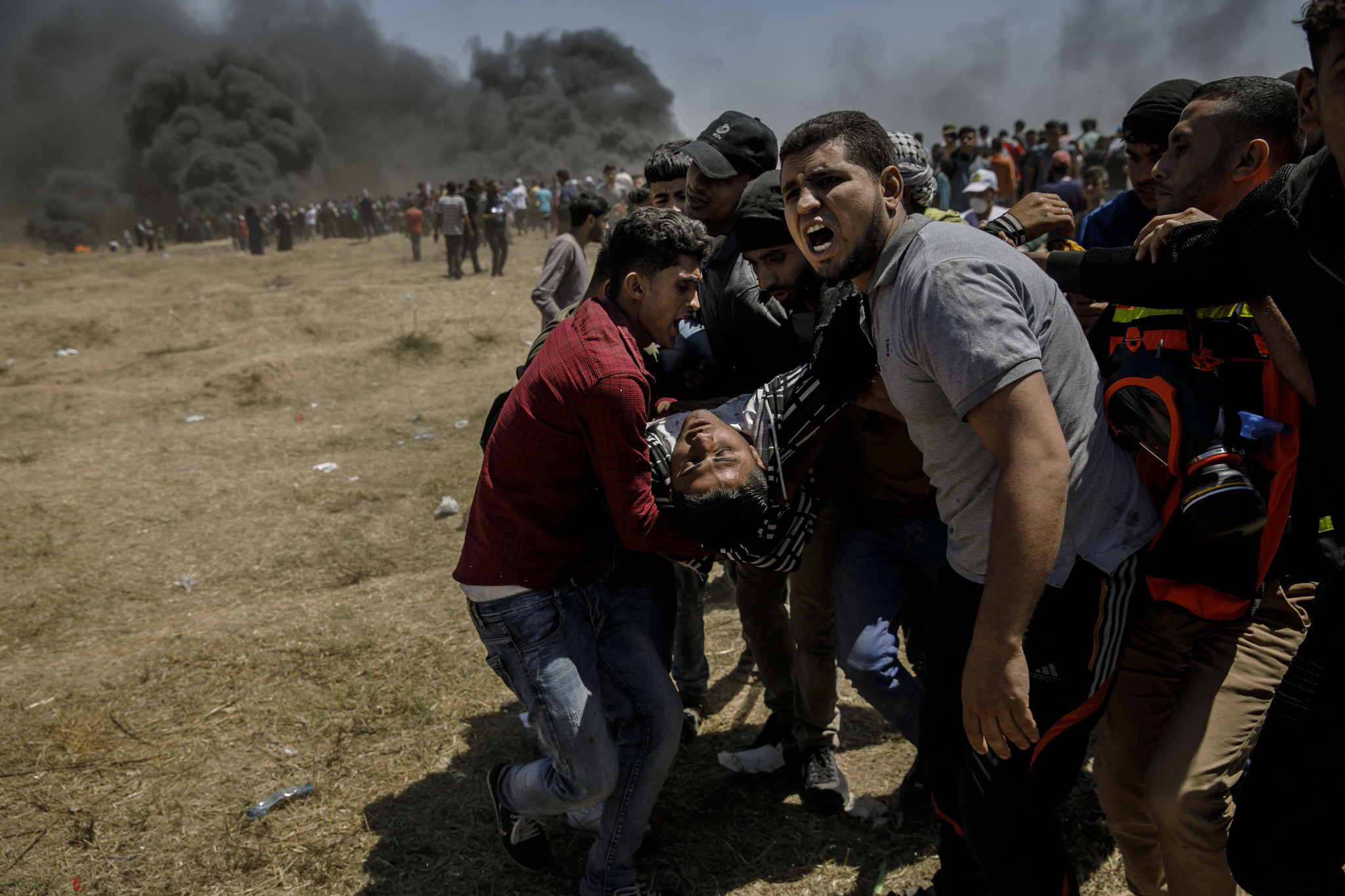 GAZA CITY, GAZA — MONDAY, MAY 14, 2018: Protesters carry away the wounded shot by Israeli forces as