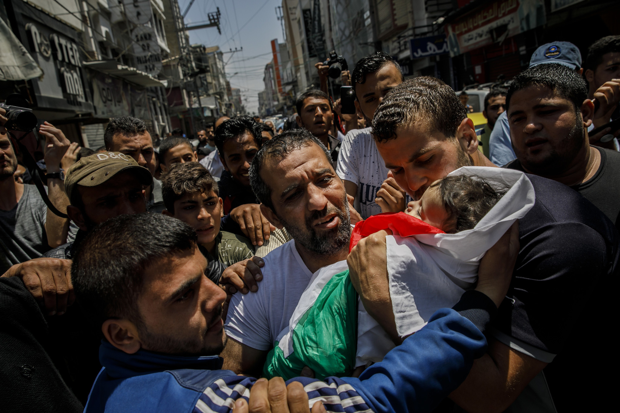 GAZA CITY, GAZA — TUESDAY, MAY 15, 2018: Family members and relatives carry the body of a dead chil