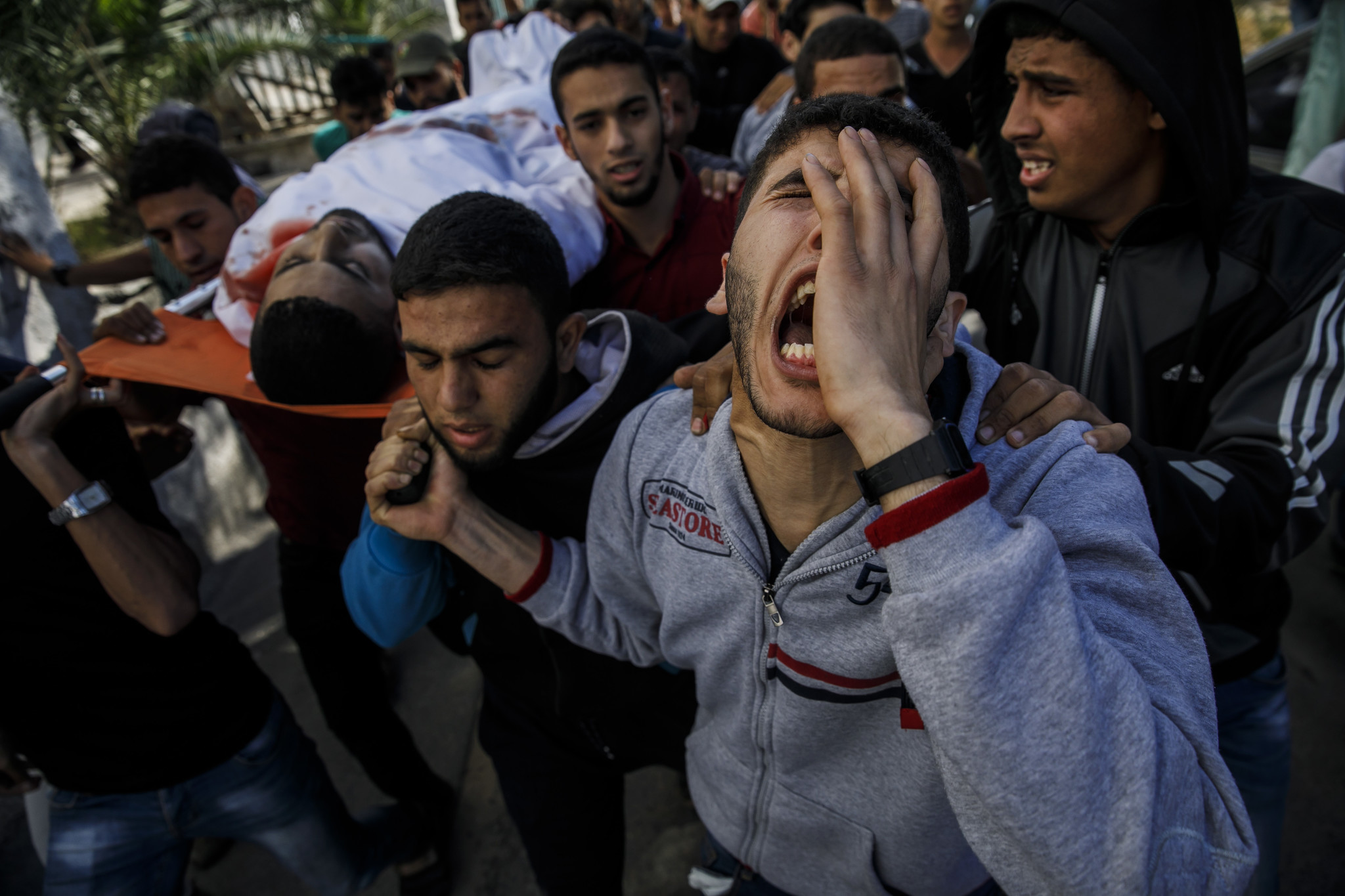 GAZA CITY, GAZA — MONDAY, MAY 14, 2018: Relatives of Taher Ahmed Madi, 25, carry his body from the