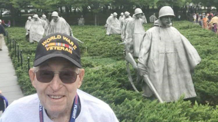 Bill Howells stands by statues of military members at the Korean War Memorial in Washington, D.C.'s West Potomac Park, near the Lincoln Memorial and Reflecting Pool.