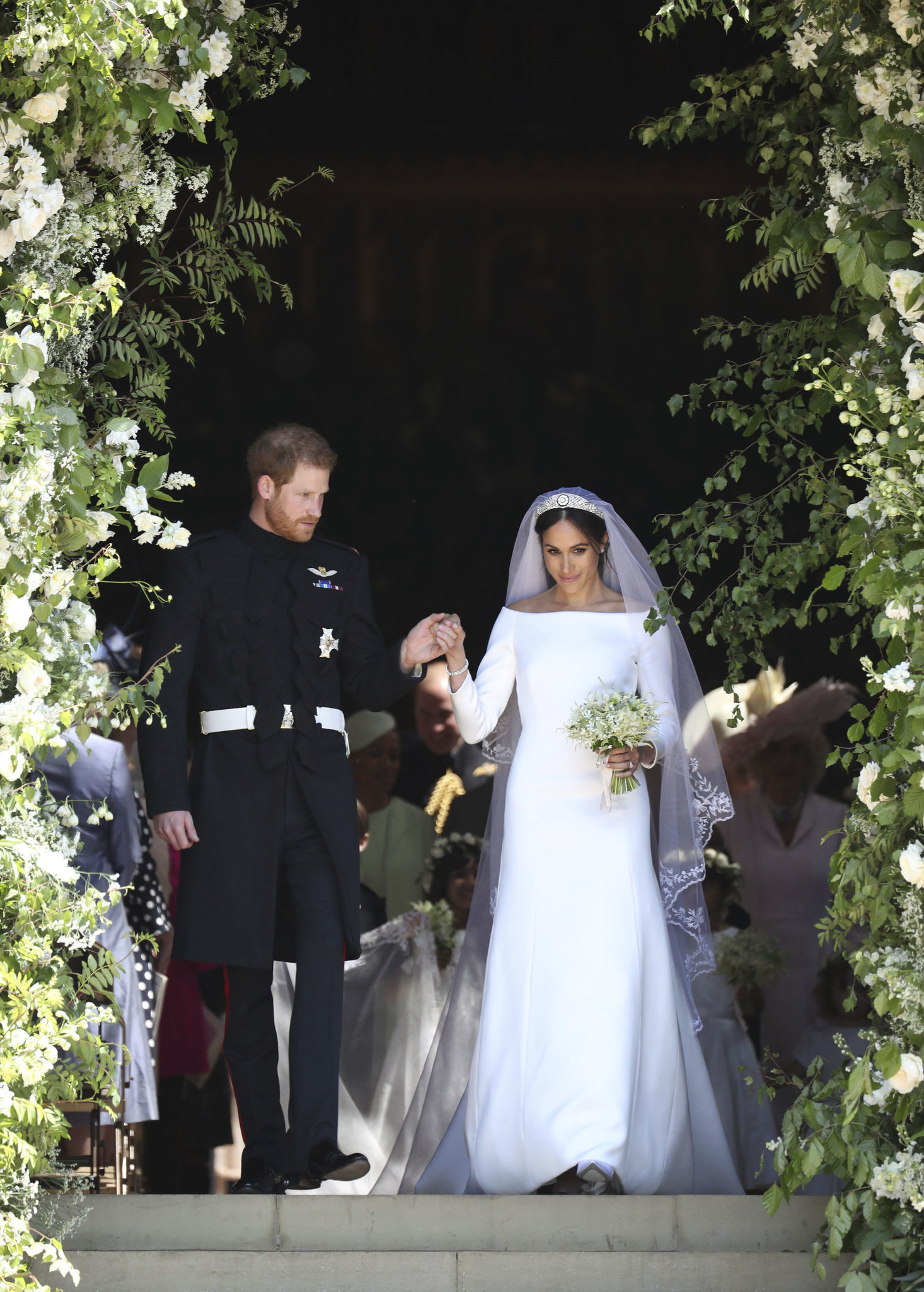 Prince Harry, left, and wife Meghan Markle — the Duke and Duchess of Sussex — on the steps of St George's Chapel at Windsor Castle following their wedding in Windsor.