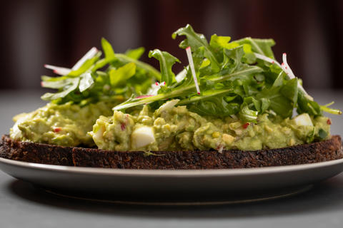 Avocado toast with lemon, shaved radish, hard-boiled egg, seeded rye and arugula.