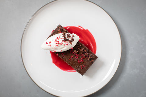 Flourless chocolate cake with whipped topping, raspberry caramel and cacao nibs.