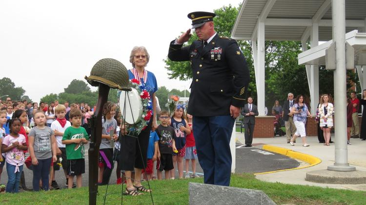 Soldier saluting memorial