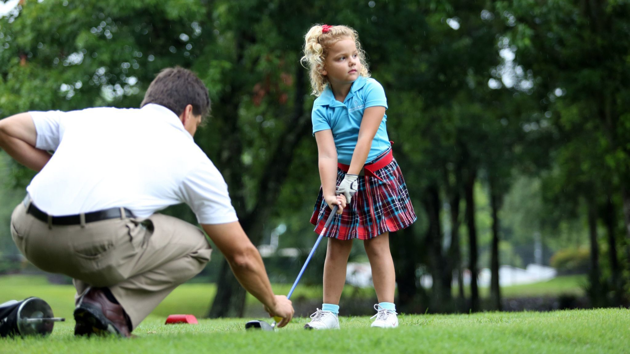 Dad Michael Dovhey sets up a ball for Bella Douvhey, 5-year-old from Oviedo, at Twin Rivers Golf Clu